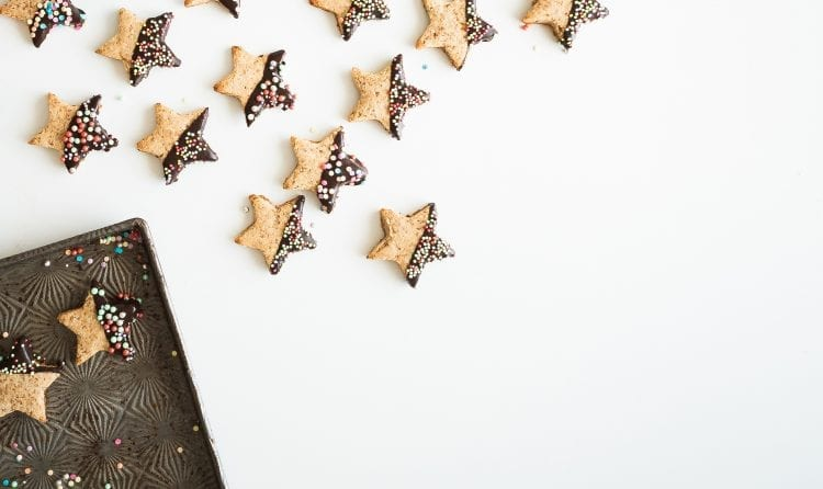 star shaped cookies, half covered in chocolate and sprinkles. alligned artistically with some on baking tray and some on a white table