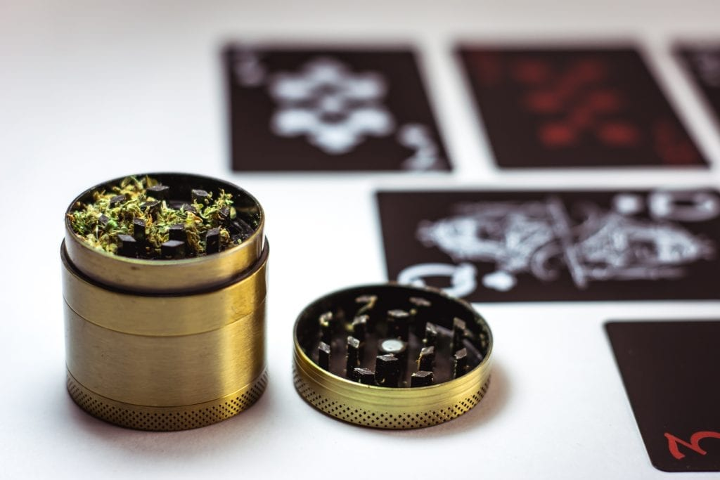 gold Cannabis grinder on a table that has stickers on it. Lid is off of the grinder and there is cannabis inside of it