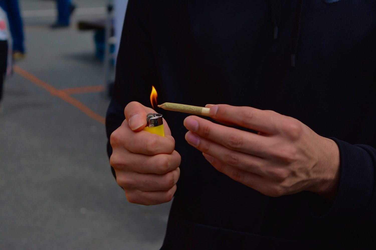 person lighting a joint at 4/20 rally. Sunset Beach Park, Vancouver, Canada