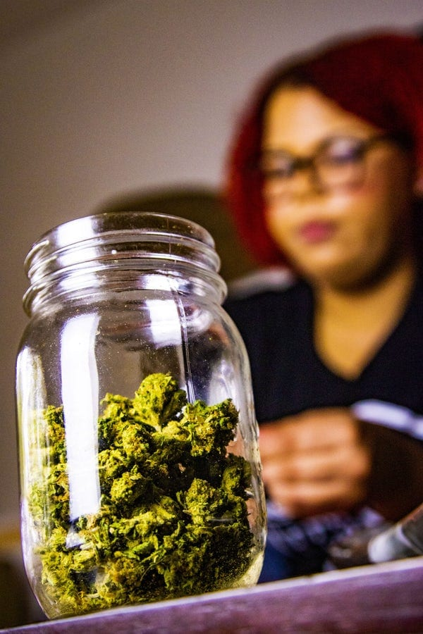 A big glass jar that's filled up with vibrant green cannabis. A person in the background rolling the weed up into a joint.