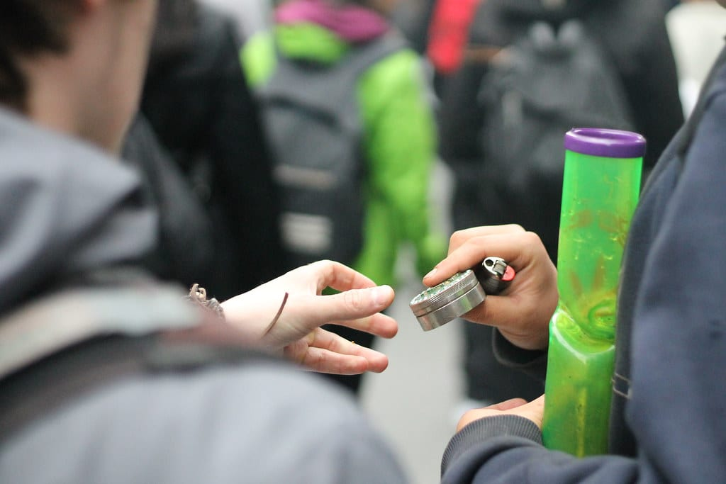 man with a bong and electric weed grinder handing the electric grinder to another person