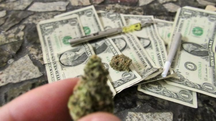 USD cash with cannabis nugs and joints on top of it. Wax pen on top of the money
