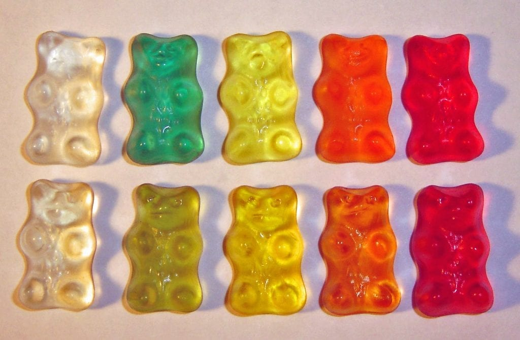 Gummy bears spread our artistically on a white surface. Red, Orange, Yellow, Green, and white.
