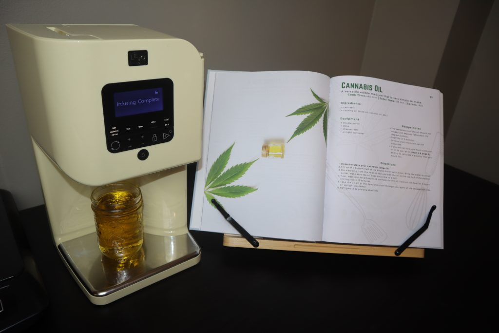 cannabis-infused oil in a levo infusion machine, beside a cannabis cookbook on a black table.