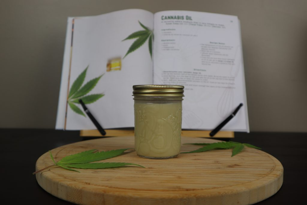 Cannabis oil inside a mason jar on a wooden cutting board. Cannabis leafs are placed on top of the cutting board and a cannabis cookbook is behind.