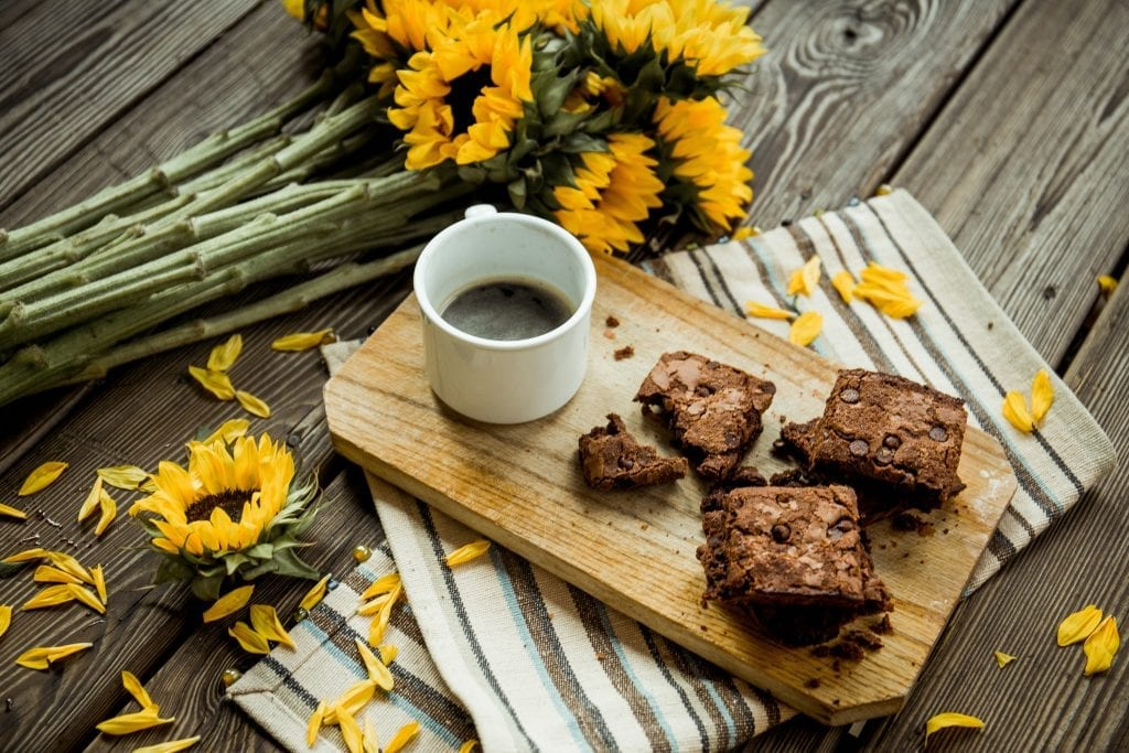 cannabis brownies and cup of coffee on a cutting board. The cutting board is on a table with sunflowers