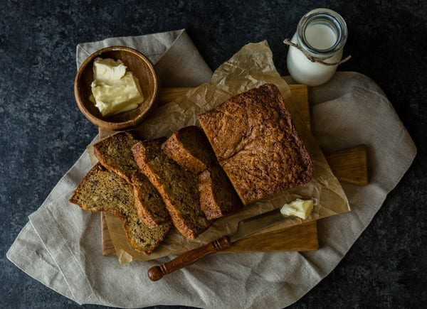 Butter beside banana bread on a cooking cloth. A glass of milk sits beside it.