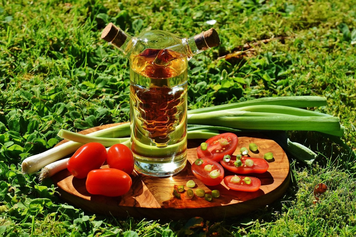 Cannabis infused cooking oil on a brown cutting board with tomatoes, onions, and veggies. This is all on bright green grass