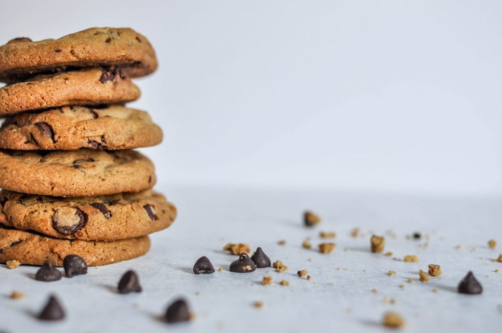 Stack of 6 weed cookies on a white table with chocolate chips. These are some of the best weed recipes.
