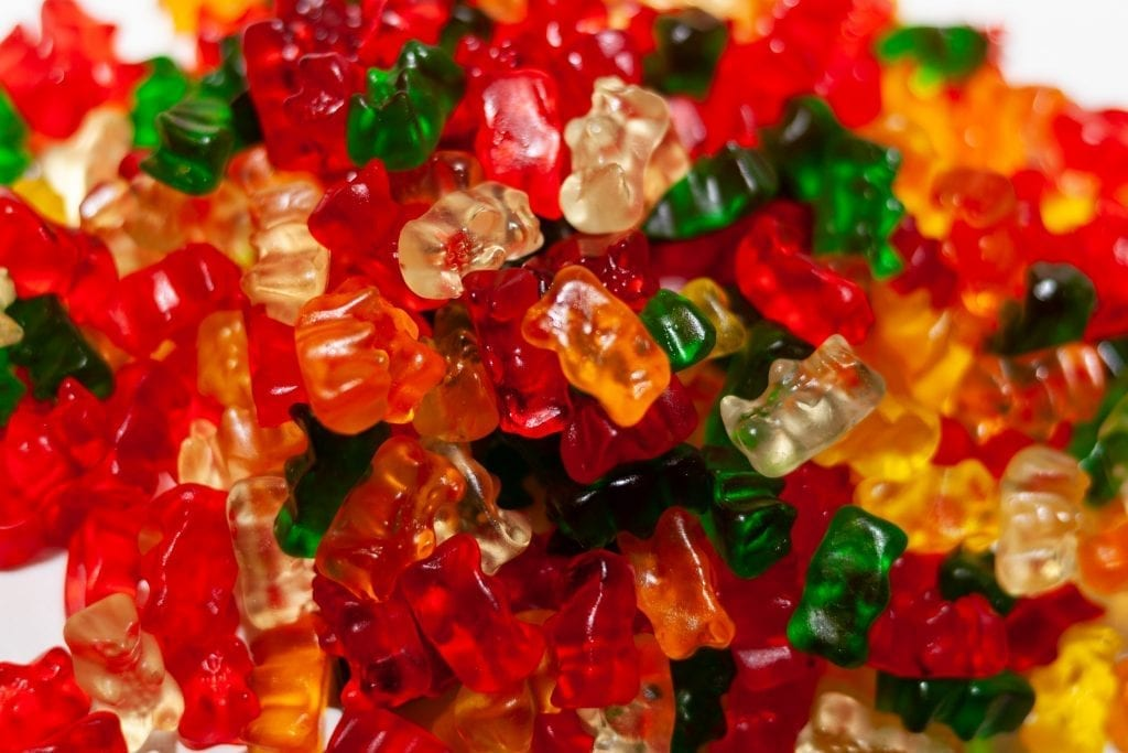 Weed infused gummy bears colored in red, orange, green, and clear.
