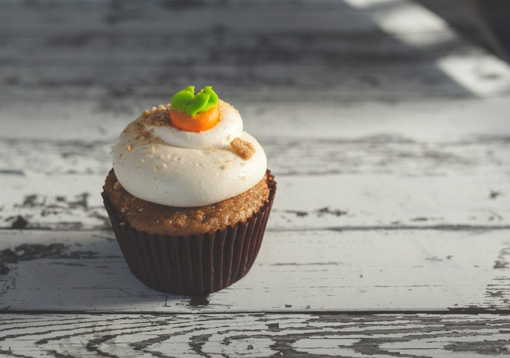 Cannabis infused pumpkin spice cupcakes with some orange and green icing on top of them.