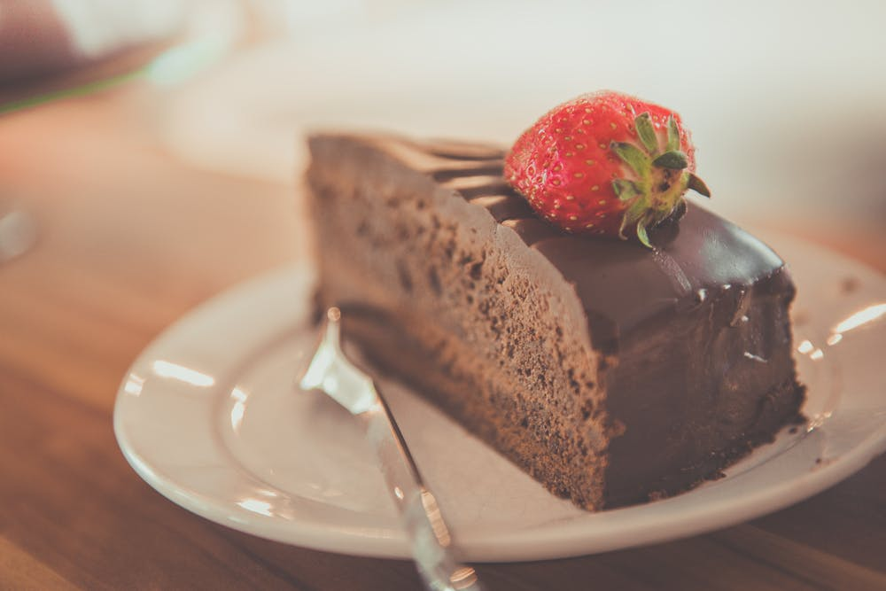 chocolate cake with a red strawberry on top of it.