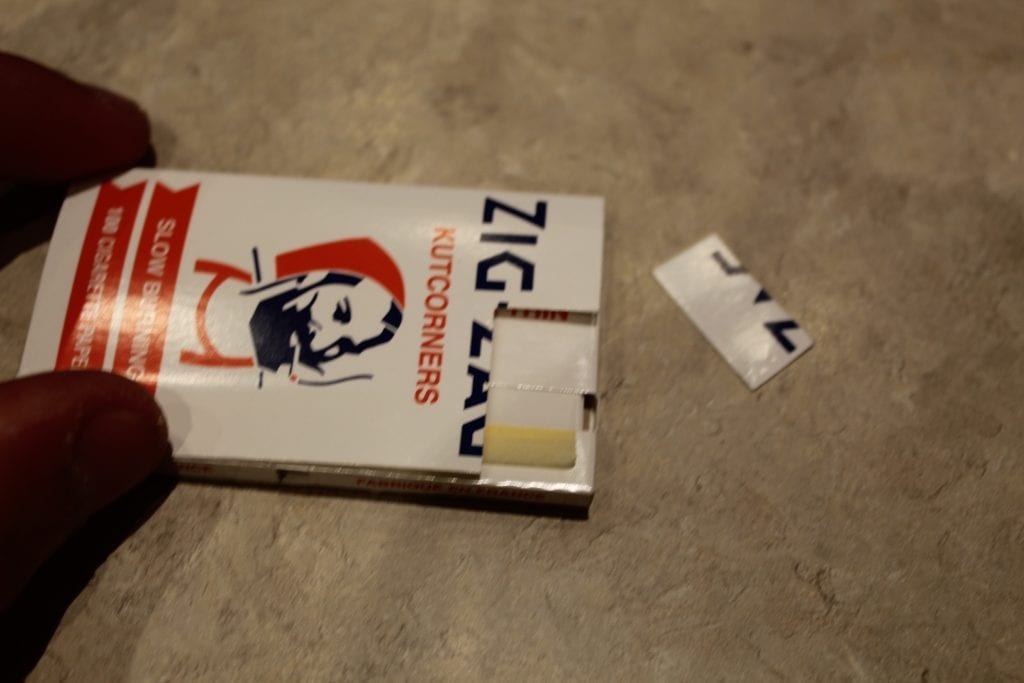 Pack of zig-zag rolling papers with filter ripped out of the corner