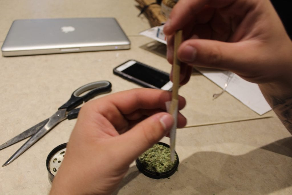 pre-rolled joint being packed down and filed with cannabis.