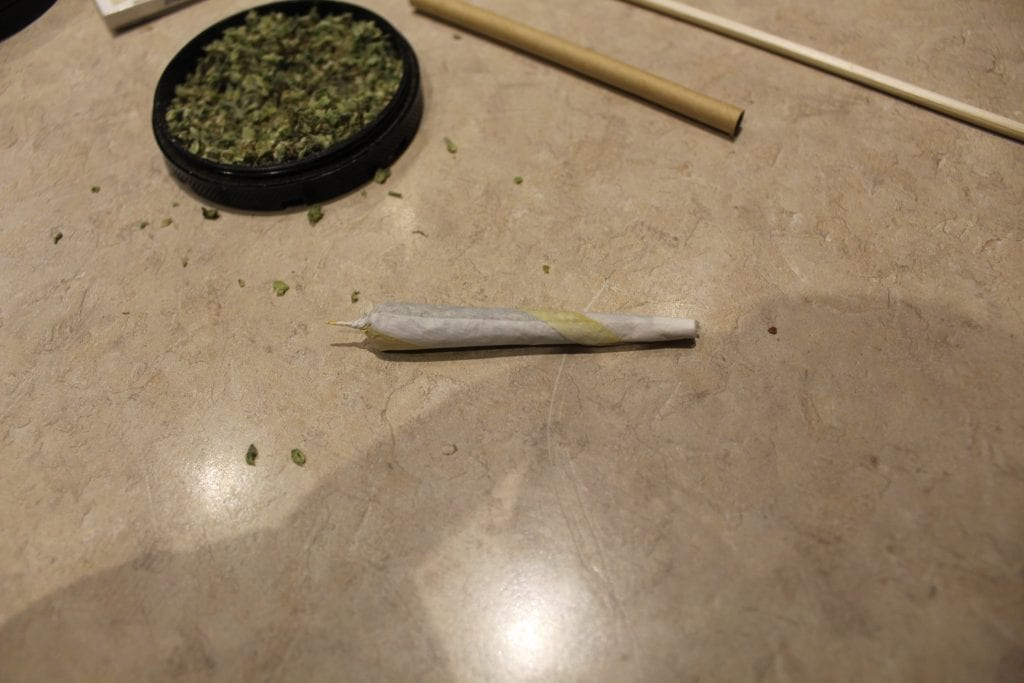 Perfectly rolled joint with cannabis behind it on a table.