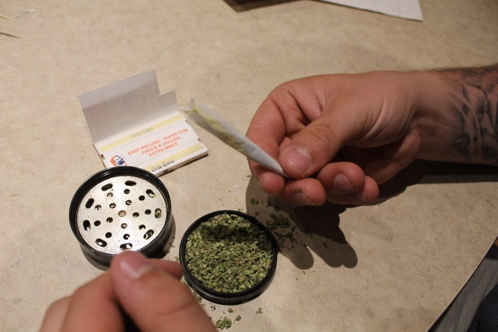 rolled joint being packed with more cannabis. Grinder full of weed and rolling papers on table beside them.