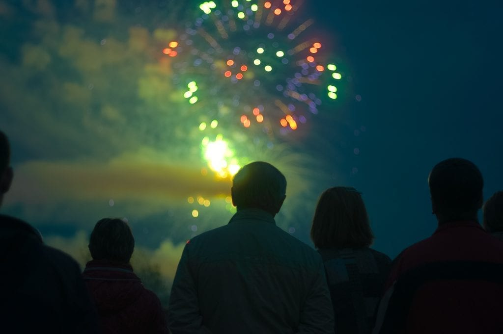 Person who is high on cannabis gazing into a firework show. how not to look high, be in darkness.