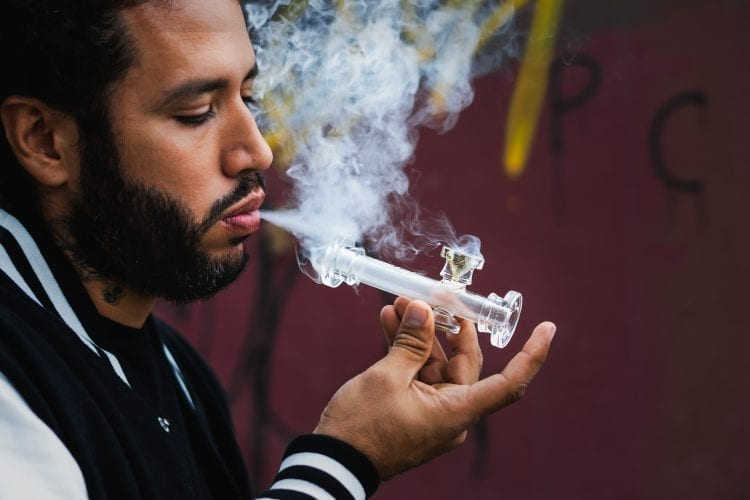 Man with beard smoking cannabis outside with a glass pipe. Smoke coming out of his mouth and the white pipe