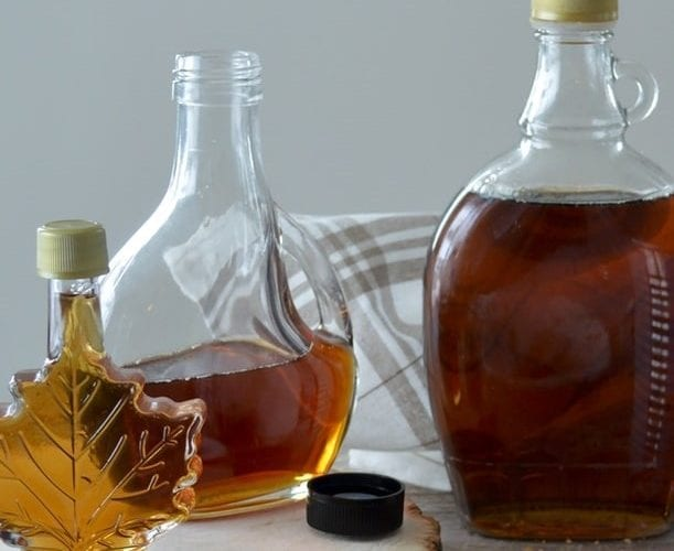 weed maple syrup cannabis edible. The maple syrup shaped bottle holds the golden color syrup inside.