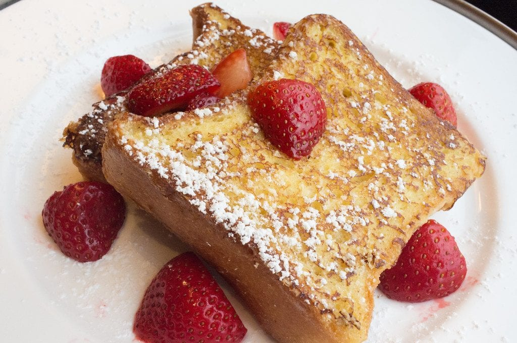 Cannabis infused french toast with strawberries and sugar on a white plate