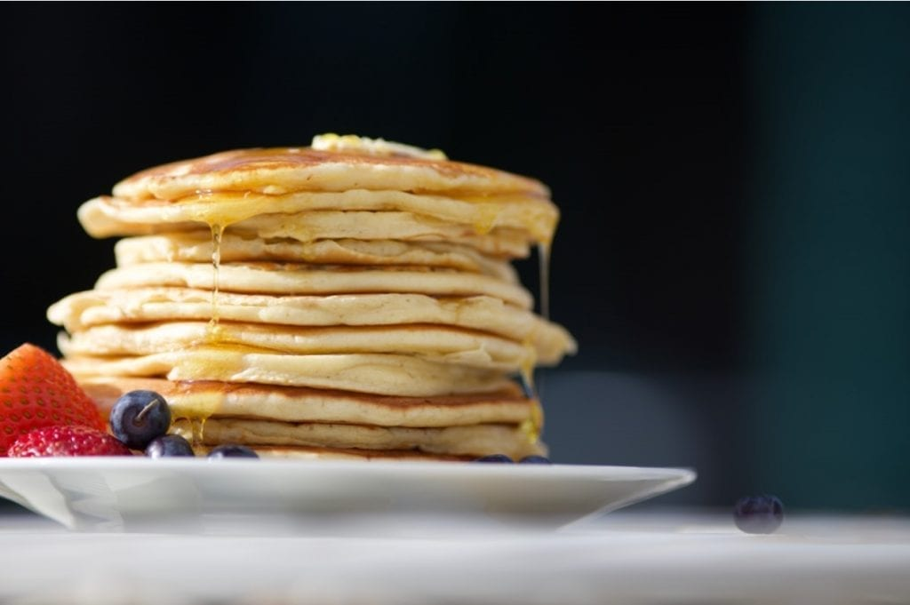 weed pancakes stacked on top of each other on a plate with butter melting overtop of them. White plate and black background