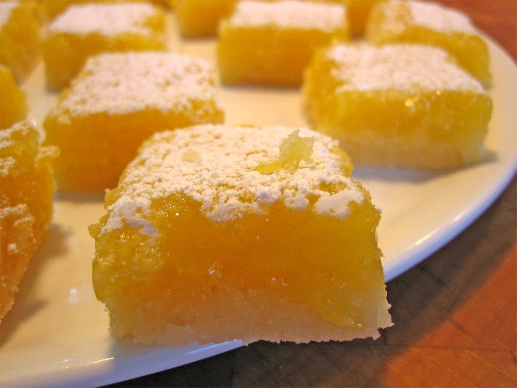 multiple weed lemon bars on a white plate. lemon squares have powder sugar on top of them