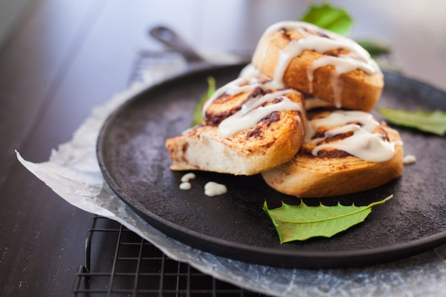 cannabis infused cinnamon rolls on a black plate with leaves beside them.