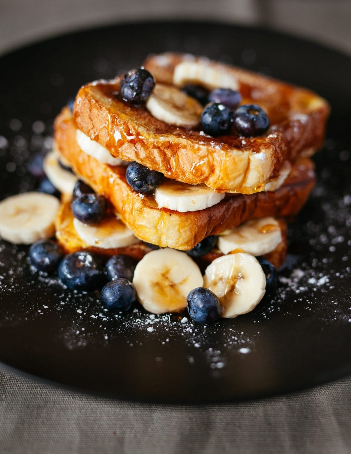 french toast on a black plate with blueberries, bananas, sugar