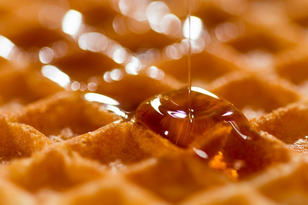 close up shot of maple syrup being poured over cannabis infused edible waffles