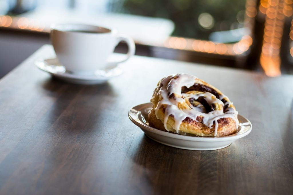 weed cinnamon rolls with white icing on the top melting over the bun.