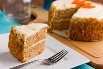 Cannabis infused carrot cake on a wooden cutting board with a slice being taken from it