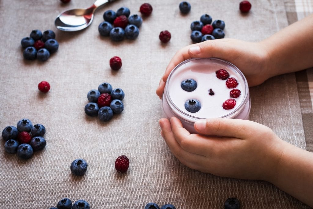 Child holding bowl of yogurt with blueberries and raspberries spread out on the table