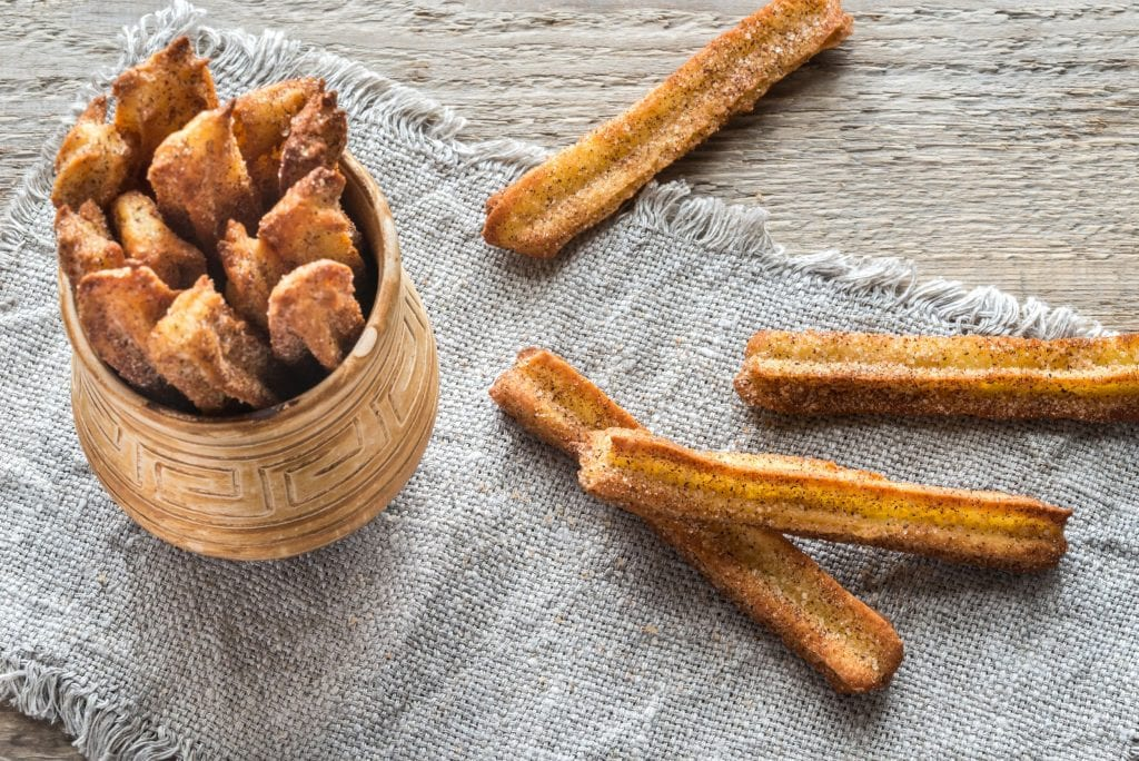 weed infused churros in a brown cup with more spread artistically around on the wooden surface