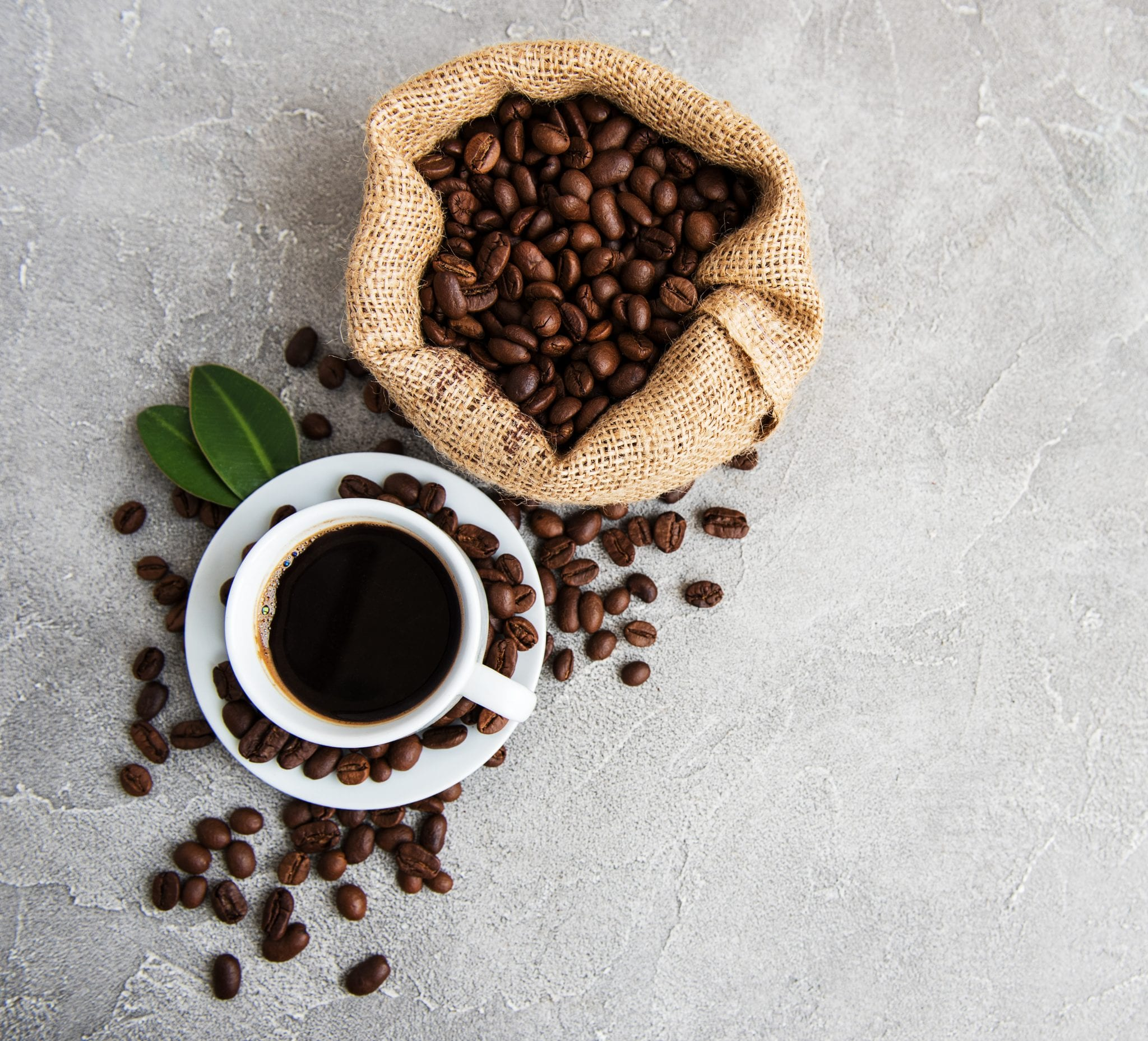 cup of weed coffee laying beside coffee beans.