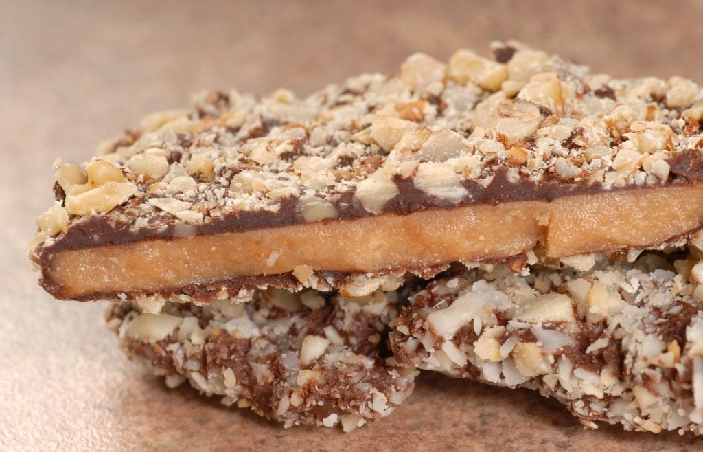 Homemade infused Chocolate English Toffee Topped with Nuts stacked on other pieces of toffee on a brown table