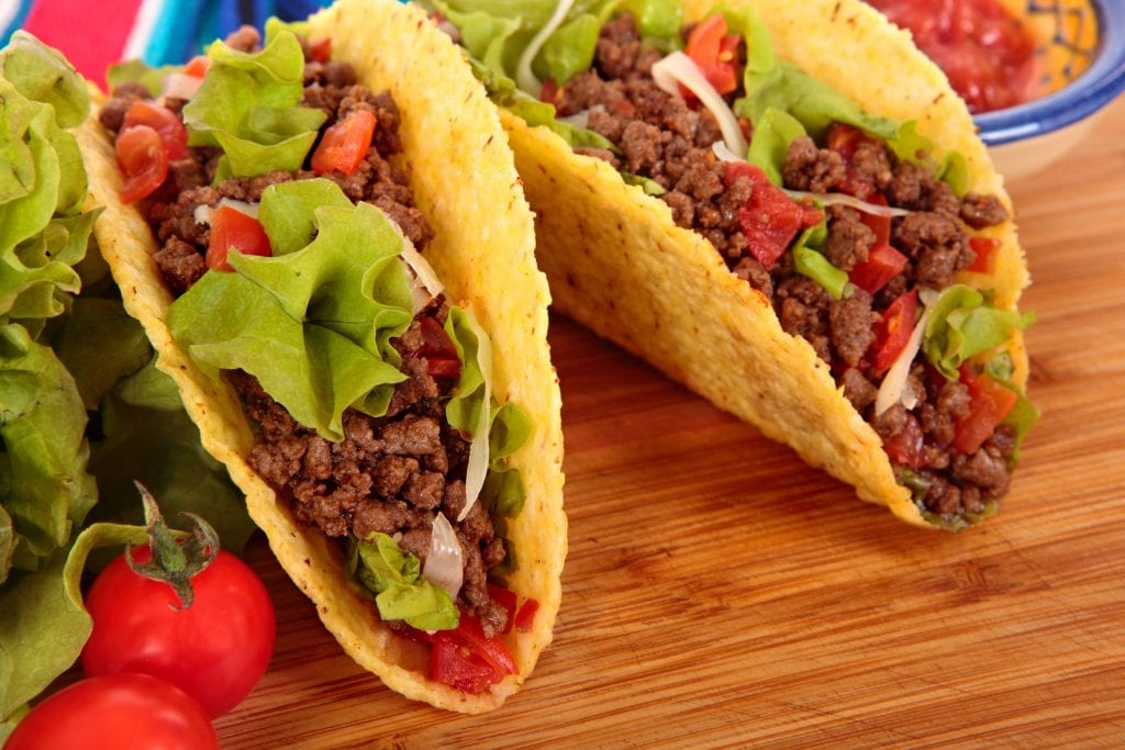 macro of two cannabis infused tacos with ground beef, tomatoes, onions, and lettuce. Salsa in the background