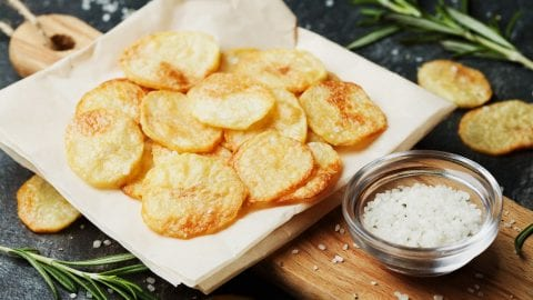 Cannabis infused potato chips and napkins which on top of the wooden cutting board with a cup of salt beside them