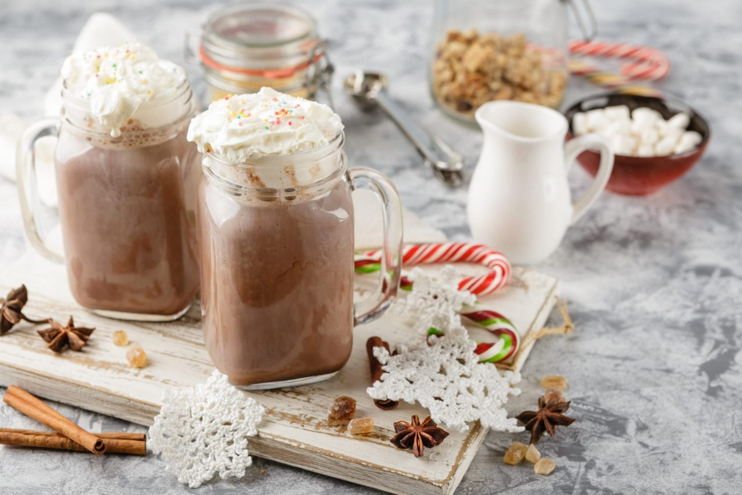 Two jars with weed hot chocolate in them on a wooden cutting board. Lots of cutlery and cups in the background