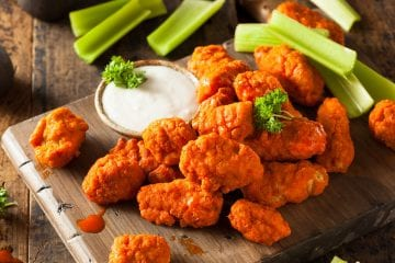 Overhead image of weed boneless buffalo wings on a wooden cutting board with dipping sauce beside the cutting board