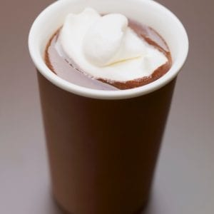 cannabis infused hot chocolate with whip cream and marshmallows on top of it. The cup is in front of a brown background