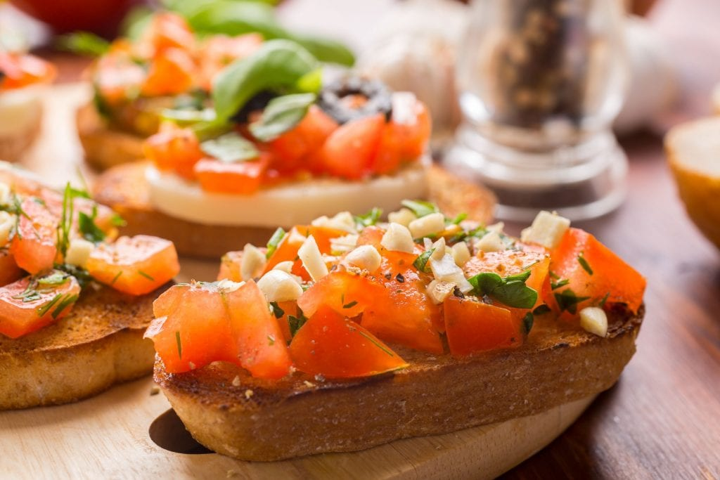 A slice of weed bruschetta I wooden cutting board With lots of other pieces of weed bruschetta in the background