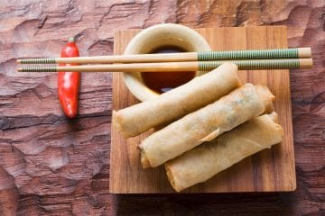 Three weed spring rolls on a wooden plate with a cup of sauce beside them. On top of the cup of sauce there is two chopsticks and a red pepper in the background