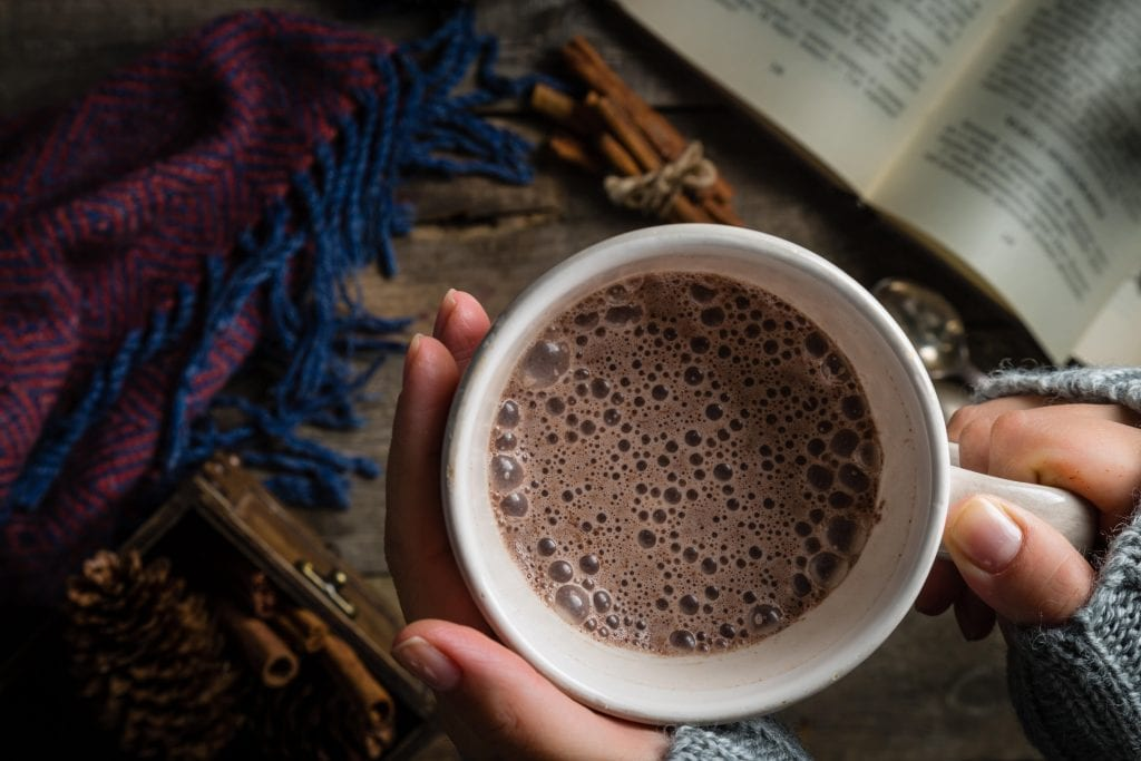 Overhead macro close up of a womans hand holding a cup of cannabis infused hot chocolate on a rustic background