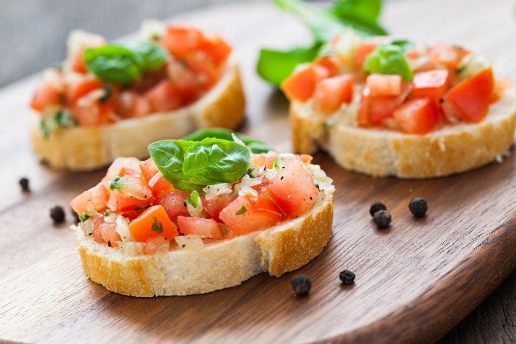 weed infused bruschetta with peppercorn beside them on a wooden cutting board