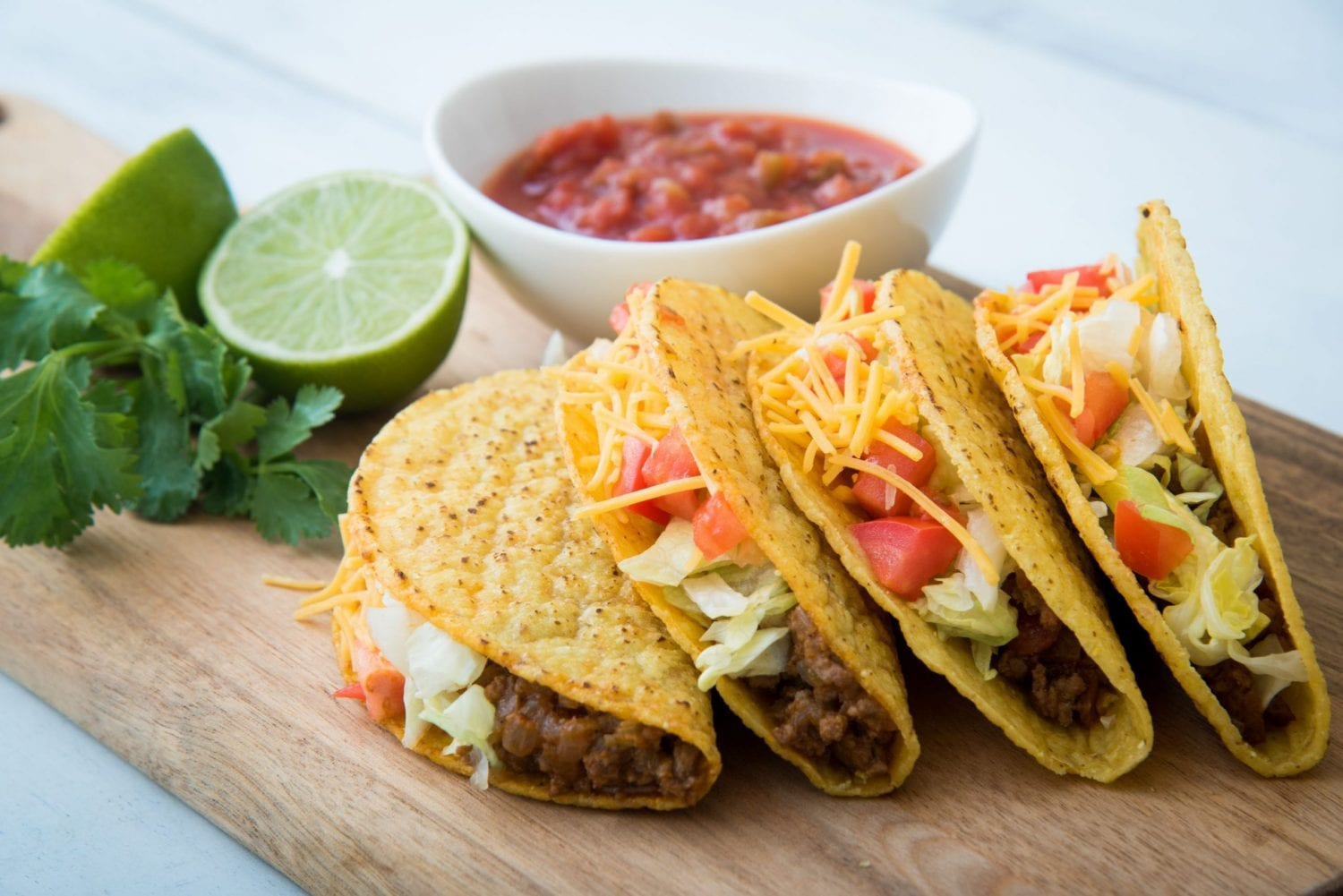 4 cannabis infused tacos with limes and salsa in the background