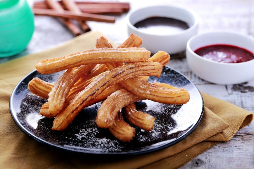 Weed infused churros on a black plate with different types of sauces in the background