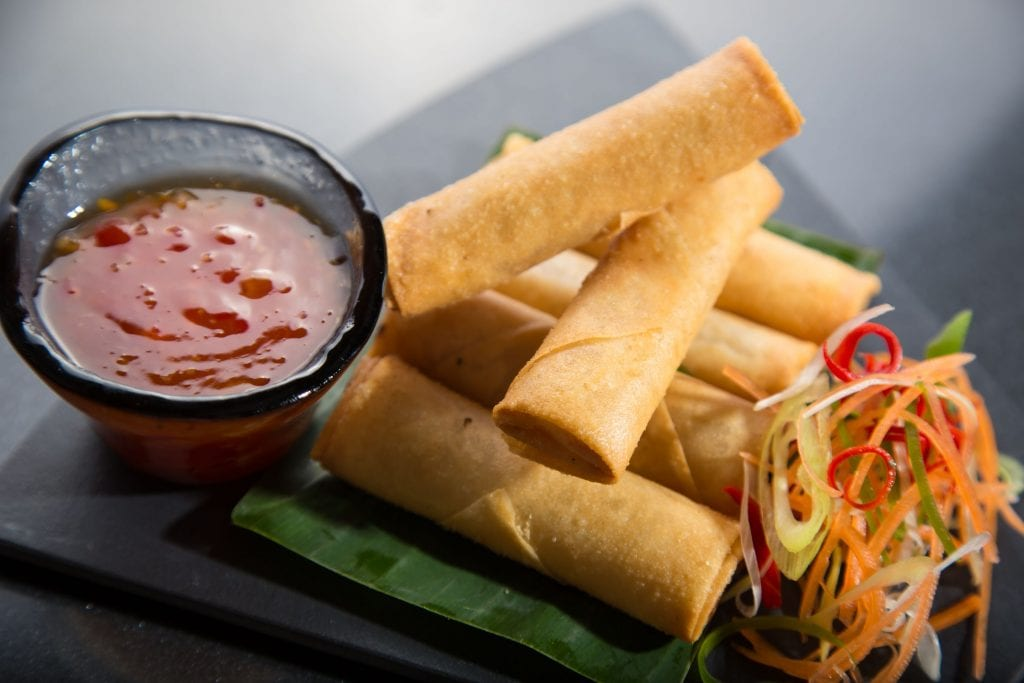 """For spring rolls infused with cannabis, place a TP on a black plate with two Kabah spring rolls. Sweet and sour sauce and vegetables next to the spring rolls on the plate """"class ="""" wp-image-9715"""