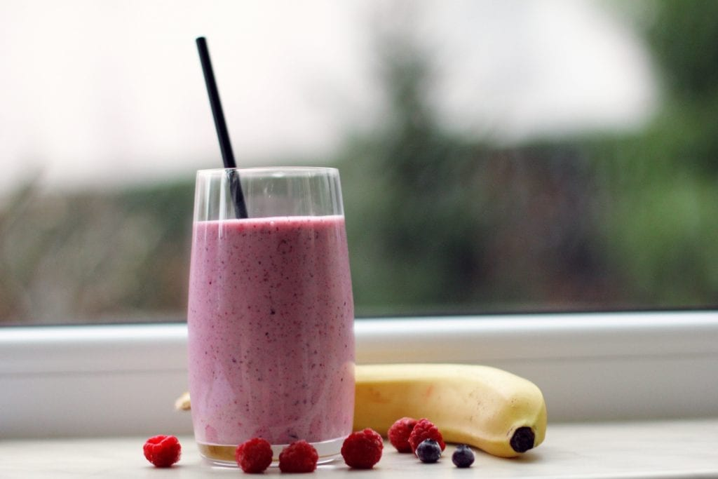 Cannabis strawberry smoothie with a black stripe in it on the table beside of banana raspberries blueberries. This is all on a window cell