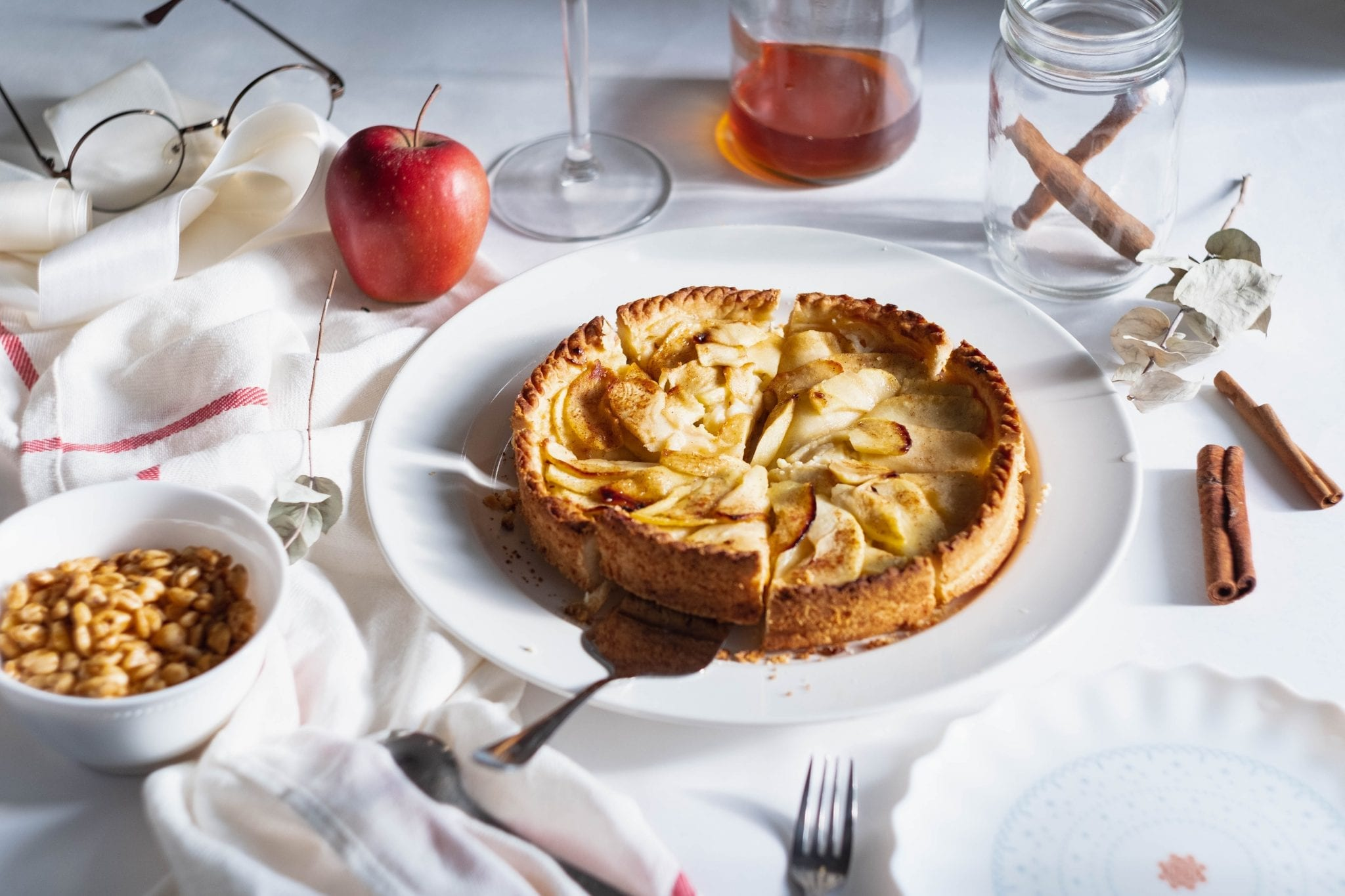 Cannabis apple pie.On a white table with a pie cutter taking a slice out of it and peanuts cinnamon and apple and other decorative items in the background