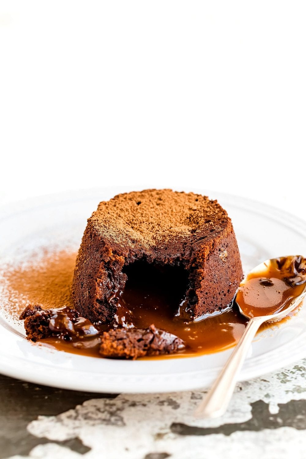 Cannabis infused lava cake on a white plate With a spoon for sale on the plate the lava cake has been cut open and is spilling onto the plate with brown powder in the back